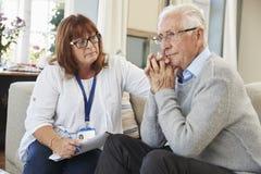 Работник поддержки навещает старший человек страдая с депрессией стоковое фото
