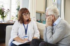 Работник поддержки навещает старший человек страдая с депрессией стоковые изображения rf