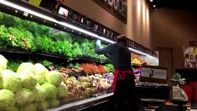 Работник показывая овощи на стеллаже для выставки товаров для продажи