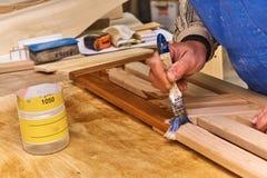 Работник покрывает панели с лаком Детализирует деревянную продукцию Стоковая Фотография
