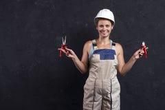 Работник построителя женщины в форме держит wirecutter Женщина электрика в шлеме Профессиональный электрический инженер стоковые фотографии rf