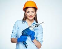 Работник построителя женщины при сверло стоя против белого backgrou Стоковая Фотография