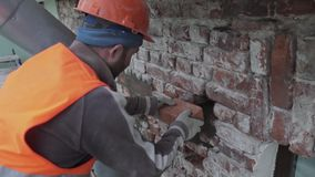 Работник построителя кладет кирпич в стену фасада и штукатурит он с большим ножом spackle акции видеоматериалы