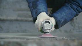Работник построителя с бетонной стеной отделкой вырезывания машины точильщика на строительной площадке зажим Работник мелет бетон акции видеоматериалы