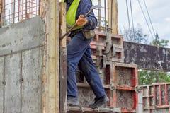 Работник построителя извлекая элементы форма-опалубкы с ломом Стоковые Фото