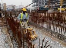 Работник построителя на уплотнении песка земном с машиной compactor плиты вибрации Стоковые Изображения RF