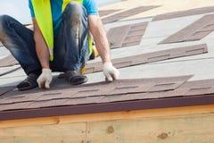 Работник построителя Roofer устанавливая гонт асфальта или плитки битума на новый дом под конструкцией стоковая фотография