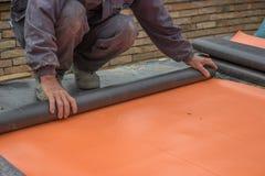 Работник подготавливая материал изоляции на стена 3 подвала стоковое фото