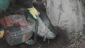 Работник при круглая пила режа бетон в пакостном рве на строительной площадке видеоматериал