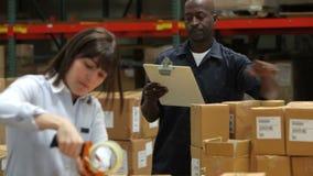 Работник проверяет доску сзажимом для бумаги как коробки уплотнений коллеги сток-видео