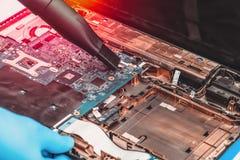 Работник пункта обслуживания профессионально приниманся за очищая ноутбук от пыли стоковое изображение