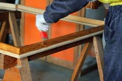 Работник плотника во время картины старой деревянной рамки Стоковые Изображения RF
