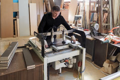 Работник работает на машине сверлить-заполнителя которая делает мебель Россия Лето 2017 стоковое фото rf