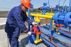 Работник работая на заводе по обработке газа Стоковые Фото