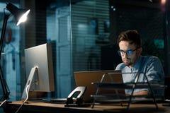 Работник работая на компьтер-книжке на ноче Стоковая Фотография RF