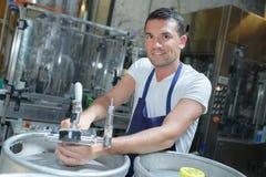 Работник работая с бочонком пива на винзаводе Стоковое Изображение