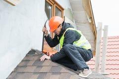 Работник разбирая гонт крыши стоковое изображение