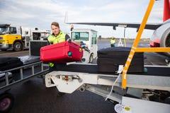 Работник разгржая багаж от транспортера прикрепленного к самолету Стоковое Изображение RF