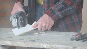 Работник режет керамические плитки с угловой машиной Много пыль видеоматериал
