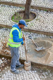 Работник ремонтируя мостоваую тротуара с традиционное и типичное handmade Стоковые Изображения RF