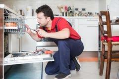 Работник ремонтируя судомойку в кухне стоковое фото