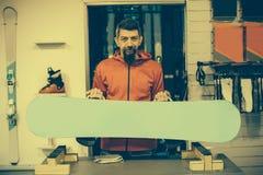 Работник ремонтной мастерской сноуборда регулирует вязки стоковые изображения