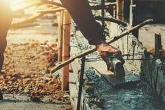 работник руки выравнивая бетон для цемента смешивания на конструкции стоковое изображение rf