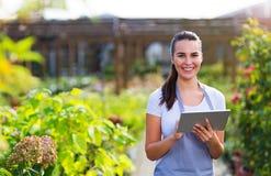 Работник садового центра используя цифровую таблетку стоковые изображения rf