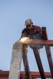 Работник сваривая сталь для того чтобы построить крышу Стоковые Изображения
