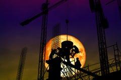 работник силуэта супер луны крови задний на конструкции стоковые изображения