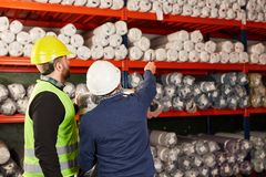Работник склада перед полкой в складе ковра стоковые фото