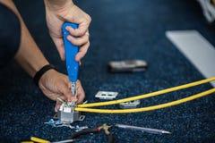 Работник соединяет кабель сети с гнездами RJ45 инструментом пунша-вниз, процессом класть локальную сеть Комплект Стоковые Фото