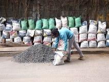 Работник строительной площадки кладет гравий в мешки и складывает их против стены стоковое изображение