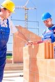 Работник строительной площадки проверяя стены здания Стоковая Фотография