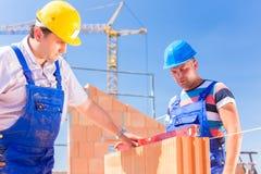 Работник строительной площадки проверяя стены здания Стоковые Изображения RF
