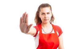 Работник супермаркета женщины делая знак стопа стоковое фото