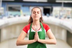 Работник супермаркета размышляя с ладонями совместно стоковые изображения rf