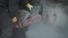 Работник с бетонной конструкцией вырезывания круглой пилы в канаве на строительной площадке видеоматериал