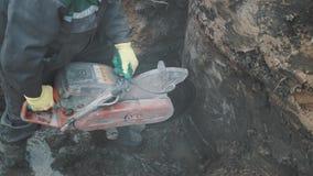 Работник с бетонной конструкцией вырезывания круглой пилы в рве на строительной площадке видеоматериал