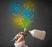 Работник с оружием airbrush красит цветастые линии и брызгает Стоковая Фотография