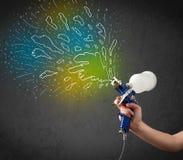 Работник с оружием airbrush красит цветастые линии и брызгает Стоковое Фото