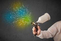 Работник с оружием airbrush красит цветастые линии и брызгает Стоковое фото RF