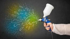 Работник с оружием airbrush красит цветастые линии и брызгает Стоковое Изображение