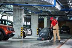 Работник с полом чистки машины в гараже стоковое фото rf