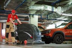 Работник с полом чистки машины в гараже стоковые изображения