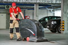 Работник с полом чистки машины в гараже стоковое изображение rf