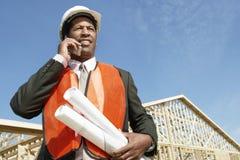 Работник с светокопиями используя сотовый телефон на строительной площадке Стоковая Фотография RF