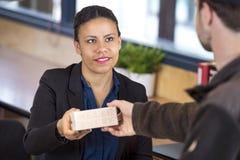 Работник службы рисепшн получая пакет от работника доставляющего покупки на дом Стоковые Изображения