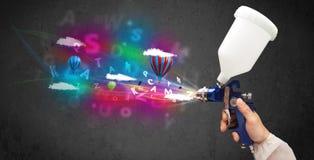 Работник с airbrush и цветастыми абстрактными облаками и воздушными шарами Стоковые Фотографии RF
