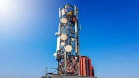 Работник техника взбираясь на рангоуте радиовещательной сети телефона устанавливая новую антенну стоковое фото